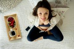 Mujer embarazada de los jóvenes, mintiendo en cama con smartphone, libro, café Imagen de archivo libre de regalías