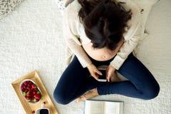Mujer embarazada de los jóvenes, mintiendo en cama con smartphone, libro, café Imagenes de archivo