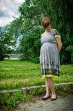 Mujer embarazada de los jóvenes que camina en un parque al lado del río Imágenes de archivo libres de regalías