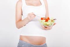 Mujer embarazada de los jóvenes que come la ensalada fresca Imágenes de archivo libres de regalías
