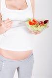 Mujer embarazada de los jóvenes que come la ensalada fresca Foto de archivo libre de regalías