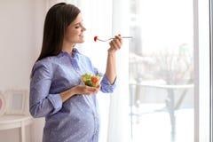Mujer embarazada de los jóvenes que come la ensalada vegetal imagenes de archivo