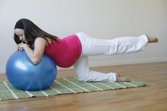 Mujer embarazada de los jóvenes que hace ejercicio del músculo de la pierna Imagen de archivo libre de regalías