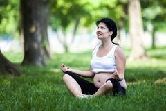 Mujer embarazada de los jóvenes que hace ejercicios de la yoga fotos de archivo