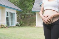 mujer embarazada de los jóvenes que hace la muestra de la forma del corazón en su panza adentro para Fotos de archivo libres de regalías