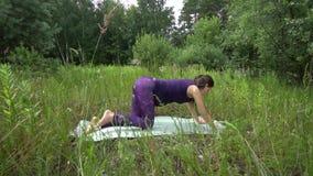 Mujer embarazada de los jóvenes que hace yoga afuera almacen de video
