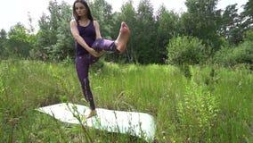 Mujer embarazada de los jóvenes que hace yoga afuera metrajes