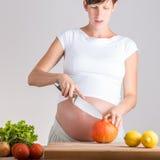 Mujer embarazada de los jóvenes que prepara verduras Foto de archivo libre de regalías