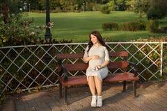 Mujer embarazada de los jóvenes que se sienta en banco en las zapatillas de deporte del parque y de los controles para recién nac Fotografía de archivo libre de regalías