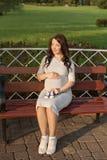 Mujer embarazada de los jóvenes que se sienta en banco en las zapatillas de deporte del parque y de los controles para recién nac Foto de archivo