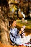 Mujer embarazada de los jóvenes que se sienta en el parque del otoño Fotos de archivo libres de regalías