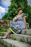 Mujer embarazada de los jóvenes que se sienta en las escaleras Imagen de archivo libre de regalías