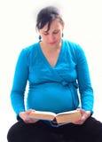 Mujer embarazada de los jóvenes que se sienta en piso y la lectura Imagenes de archivo