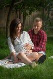 Mujer embarazada de los jóvenes y su marido que se sientan en el jardín imagen de archivo