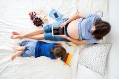 Mujer embarazada de los jóvenes y su niño, mintiendo en cama con la tableta Imagenes de archivo