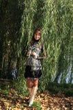 Mujer embarazada de los jóvenes por el árbol de sauce Fotografía de archivo