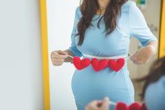Mujer embarazada del asiático con los accesorios de la forma del corazón en su panza Imagenes de archivo