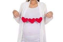 Mujer embarazada del asiático que presenta con los accesorios de la forma del corazón en ella Foto de archivo libre de regalías