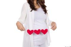Mujer embarazada del asiático que presenta con los accesorios de la forma del corazón en ella Imagen de archivo libre de regalías