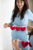 Mujer embarazada del asiático que presenta delante de un espejo con forma del corazón Foto de archivo libre de regalías