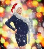 Mujer embarazada del día de fiesta de la Navidad en el sombrero de santa Foto de archivo