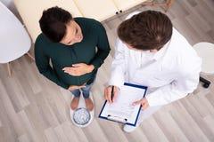 Mujer embarazada del doctor Measuring Weight Of foto de archivo
