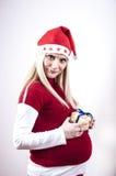 Mujer embarazada del pánico con el sombrero y el regalo de la Navidad Imágenes de archivo libres de regalías