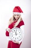 Mujer embarazada del pánico con el sombrero y el reloj de la Navidad Fotos de archivo libres de regalías