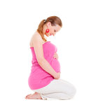 Mujer embarazada del smiley que se sienta en el suelo Fotos de archivo