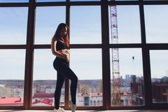 Mujer embarazada deportiva que hace ejercicios en casa fotos de archivo