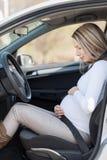 Mujer embarazada detrás del volante que tiene contracciones Imagenes de archivo