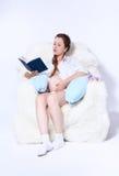 Mujer embarazada en butaca Fotos de archivo libres de regalías