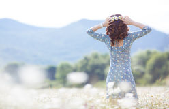 Mujer embarazada en campo con el manojo de margaritas Imagen de archivo libre de regalías