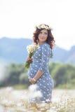 Mujer embarazada en campo con el manojo de margaritas Imagen de archivo