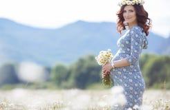 Mujer embarazada en campo con el manojo de margaritas Fotos de archivo libres de regalías