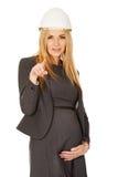 Mujer embarazada en el casco blanco que señala en usted Foto de archivo