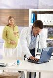 Mujer embarazada en el doctor Fotos de archivo