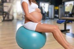 Mujer embarazada en el estudio del gimnasio foto de archivo