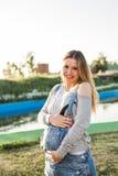 Mujer embarazada en el parque, vientre conmovedor Foto de archivo libre de regalías