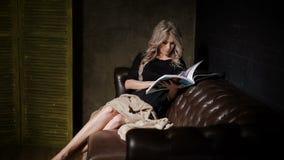 Mujer embarazada en el vestido negro hermoso que se sienta en el cuarto oscuro en el sofá de cuero marrón grande con la tela esco almacen de video
