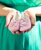 Mujer embarazada en el vientre verde del vestido que lleva a cabo los botines rosados del bebé, e Fotos de archivo libres de regalías
