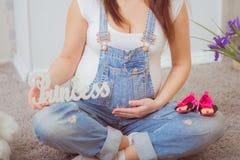 Mujer embarazada en guardapolvos del dril de algodón Imágenes de archivo libres de regalías