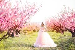 Mujer embarazada en jardín del flor de la primavera Imagenes de archivo
