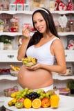 Mujer embarazada en la cocina que come la ensalada de fruta Dieta sana y vitaminas durante los meses pasados del embarazo Foto de archivo libre de regalías