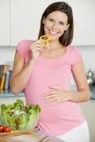 Mujer embarazada en la cocina que hace una ensalada Foto de archivo