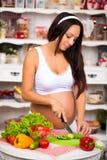 Mujer embarazada en la cocina que prepara una ensalada vegetal Nutritivo sano Los meses pasados del embarazo Imagenes de archivo