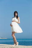 Mujer embarazada en la orilla del mar Imágenes de archivo libres de regalías