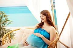 Mujer embarazada en la playa en casa de planta baja Imágenes de archivo libres de regalías