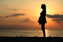 Mujer embarazada en la puesta del sol Foto de archivo libre de regalías