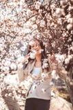 Mujer embarazada en las ramas florecientes Imagen de archivo